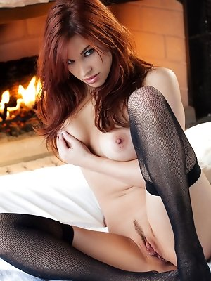 Check out this awesome set of the ravishing redhead Sabrina Maree slipping off her black lacy lingerie and getting cozy naked in front of a roaring fi